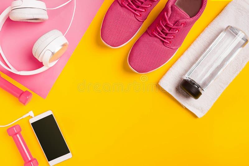 Accessoires de forme physique sur un fond jaune Espadrilles, bouteille de l'eau, écouteurs et haltères photo libre de droits