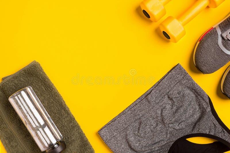Accessoires de forme physique sur un fond jaune Les espadrilles, la bouteille de l'eau, futés, serviette et sport complètent images libres de droits