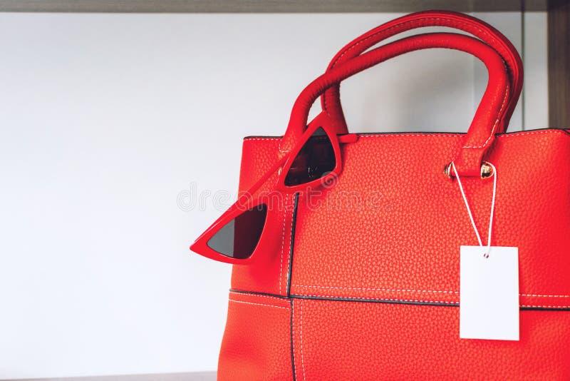 Accessoires de mode rouges femelles Sac à main rouge de femmes et lunettes de soleil rouges à la mode de plot réflectorisé sur l' image stock