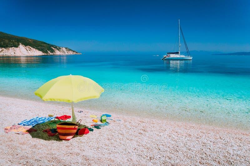 Accessoires de parapluie et de plage sur Pebble Beach le jour paresseux d'été Le bateau à voile reste à l'ancre dans clair comme  photo stock