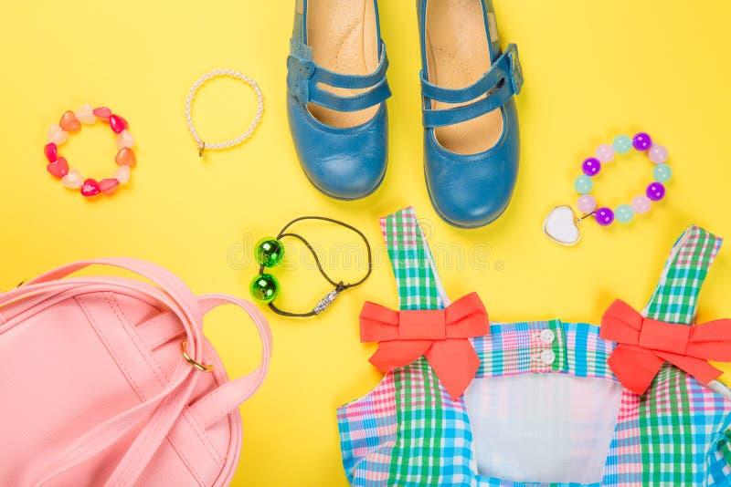 Accessoires de petite fille Sac rose avec la robe, l'anneau, les liens de cheveux et les chaussures colorés sur le fond jaune Vue photo libre de droits