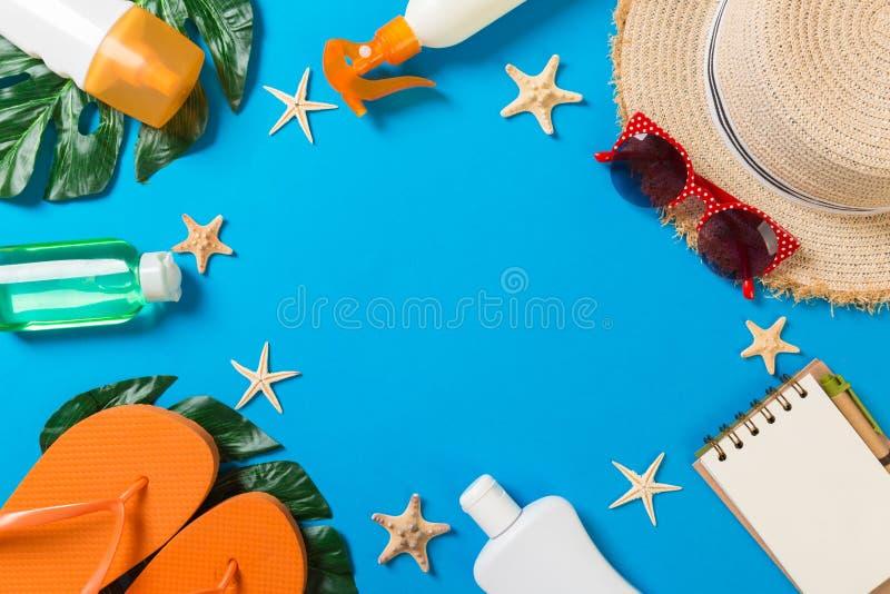 Accessoires de plage avec le chapeau de paille, la bouteille de protection solaire et seastar sur la vue supérieure de fond bleu  images stock