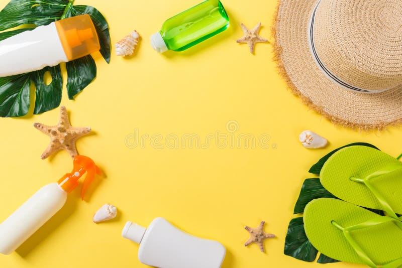 Accessoires de plage avec le chapeau de paille, la bouteille de protection solaire et seastar sur la vue supérieure de fond de ye photos libres de droits