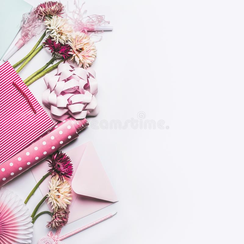 Accessoires de salutation plaçant avec les fleurs, l'arc, le ruban, le papier rose d'emballage cadeau et le panier sur le fond de photo libre de droits