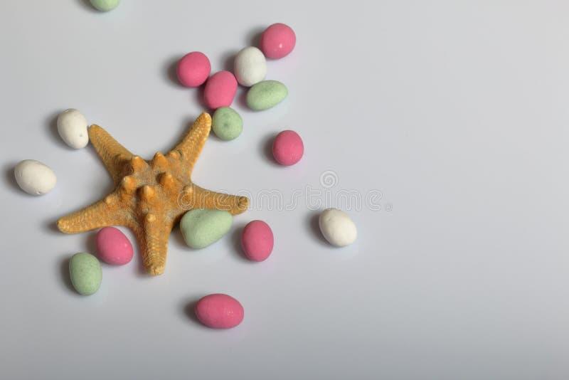 Accessoires de vacances d'été Cailloux et étoiles de mer colorés sur un fond blanc image stock