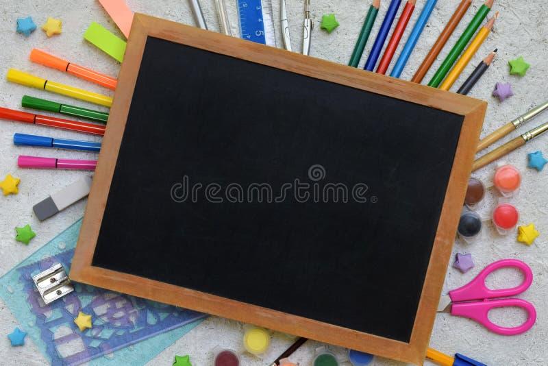 Accessoires et approvisionnements d'école : crayons, marqueurs, peintures, stylos, tableau noir pour des inscriptions sur un fond photo stock