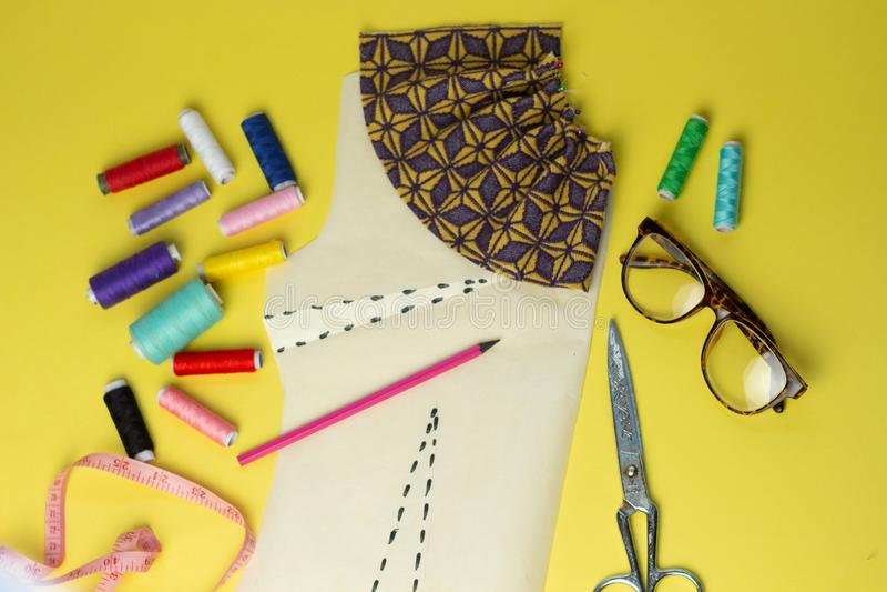 Accessoires et tissu de couture sur un fond de yelow Fils de couture, goupilles, modèle et centimètre de couture Pour coudre à la photographie stock libre de droits
