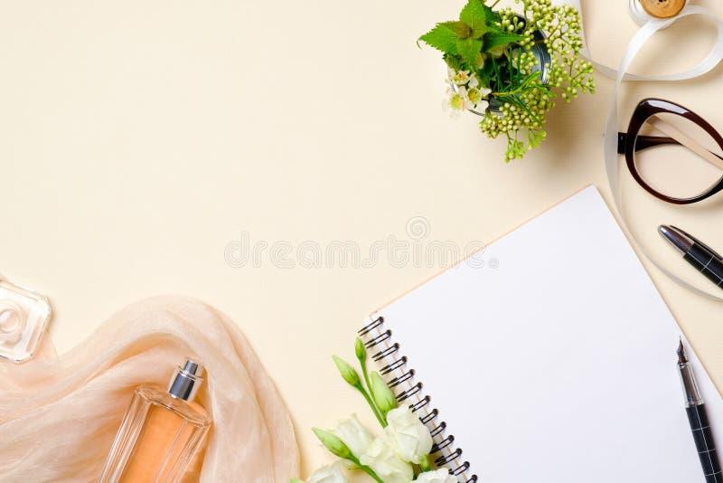 Accessoires féminins de configuration d'appartement, cosmétique de beauté, verres, fleurs de roses sur le fond beige de couleurs  photos stock