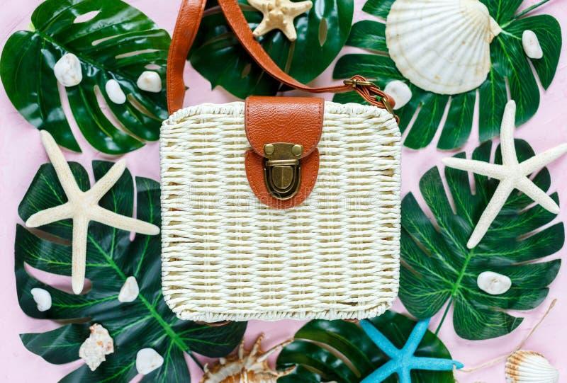 Accessoires femelles de voyageur sur le fond rose avec le sac élégant blanc de rotin de mode, coquilles, feuilles tropicales de m photo stock