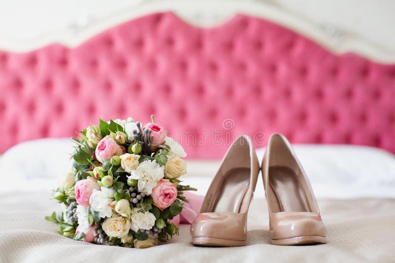 Accessoires nuptiales : chaussures et bouquet beiges image stock