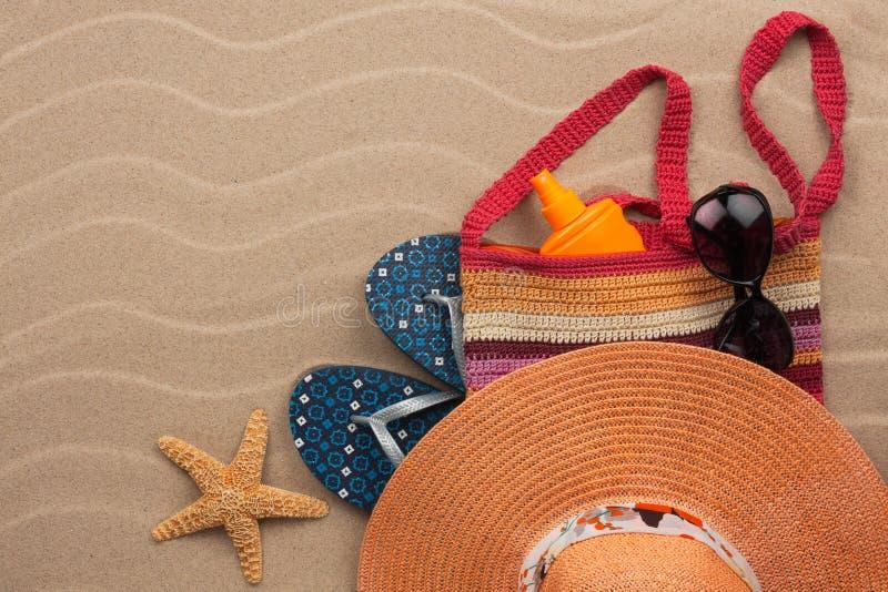 Accessoires pour la plage se trouvant sur le sable photo stock