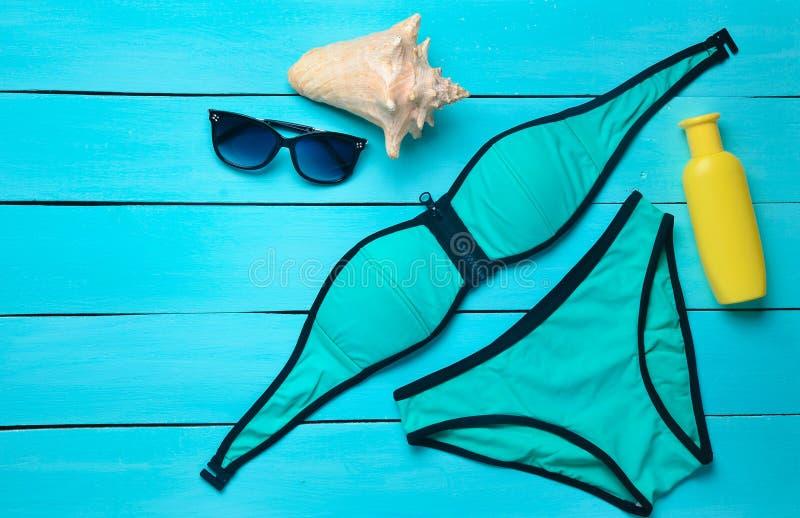 Accessoires pour la station de vacances sur la plage sur un fond en bois bleu Maillot de bain, sunblock, lunettes de soleil, coqu images libres de droits