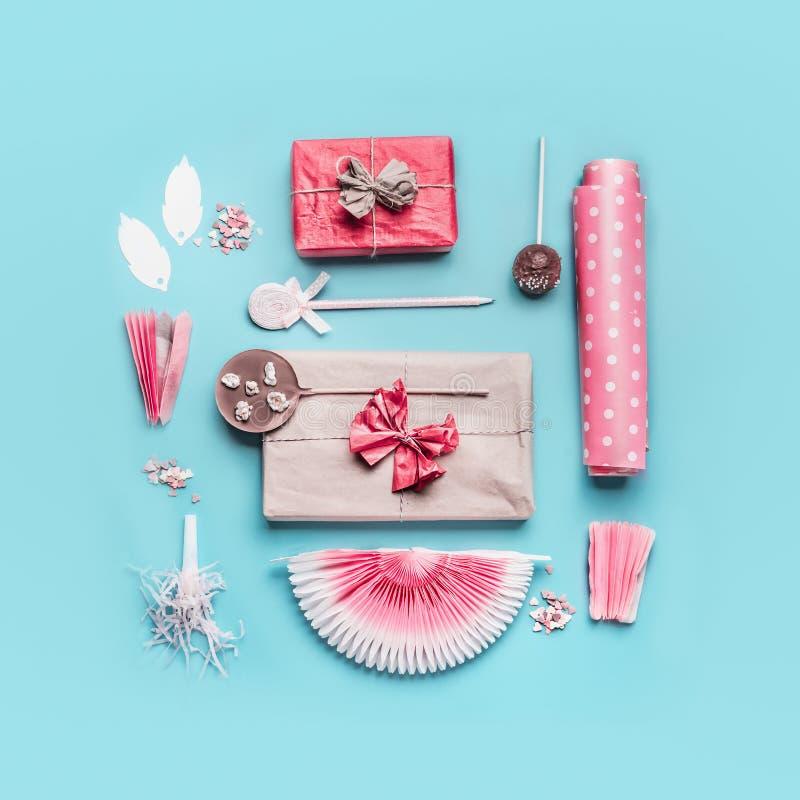 Accessoires roses de partie de vacances d'anniversaire : boîte-cadeau avec le ruban, le papier d'emballage, les bruits de sucette photos libres de droits