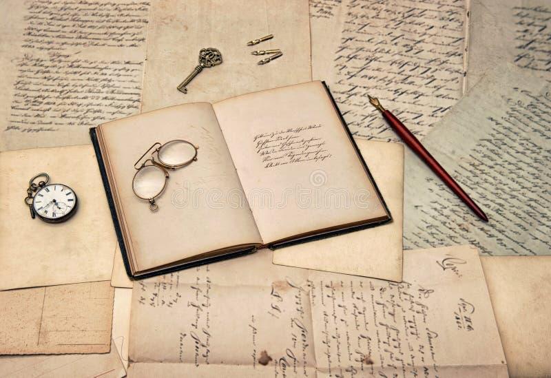 Accessori antichi di scrittura, libro aperto del diario, vecchie lettere e po immagini stock libere da diritti