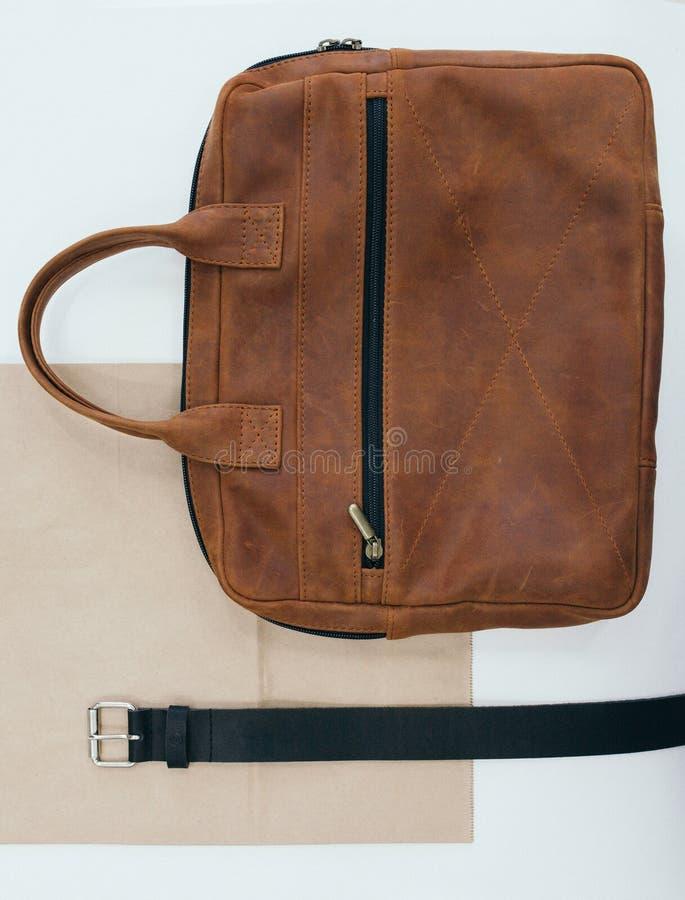 Accessori del ` s degli uomini La cinghia di cuoio e una borsa che si trovano su una tavola immagini stock libere da diritti