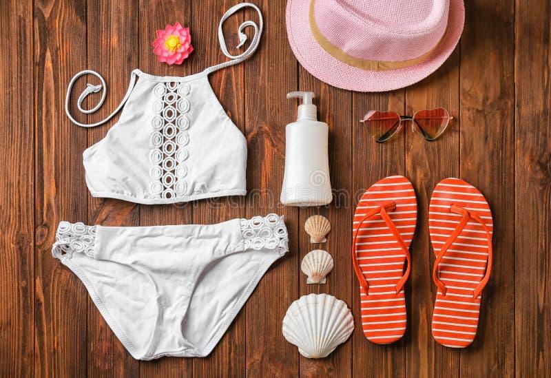 Accessori del vestito e della spiaggia di nuoto su fondo di legno fotografia stock