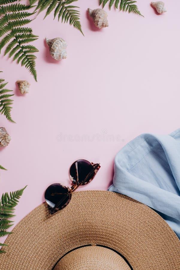 Accessori del viaggiatore, rami tropicali della foglia della felce, cappello, occhiali da sole, abbigliamento e conchiglia su fon fotografie stock