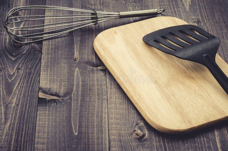 Accessori della cucina su una tavola scura di legno/accessori della cucina su una tavola scura di legno modificato Con lo spazio  immagine stock libera da diritti