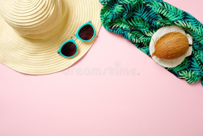 Accessori della spiaggia delle donne: cappello di paglia, occhiali da sole, noce di cocco, sciarpa verde su fondo rosa Concetto d fotografia stock libera da diritti