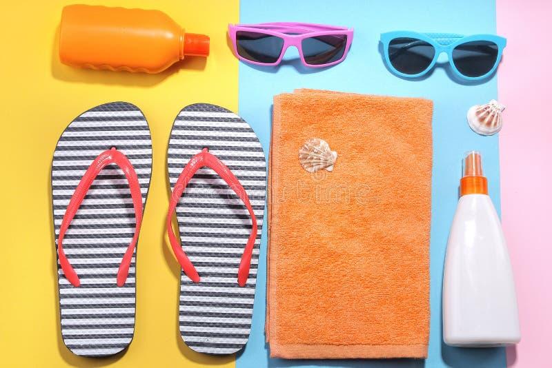 Accessori della spiaggia Vario screma, vetri, cappello ed asciugamano con le conchiglie su un fondo colorato Disposizione piana fotografia stock libera da diritti