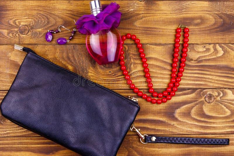 Accessori delle donne su fondo di legno Innesti la borsa, la bottiglia di profumo, la collana e gli orecchini sulla tavola di leg fotografia stock libera da diritti