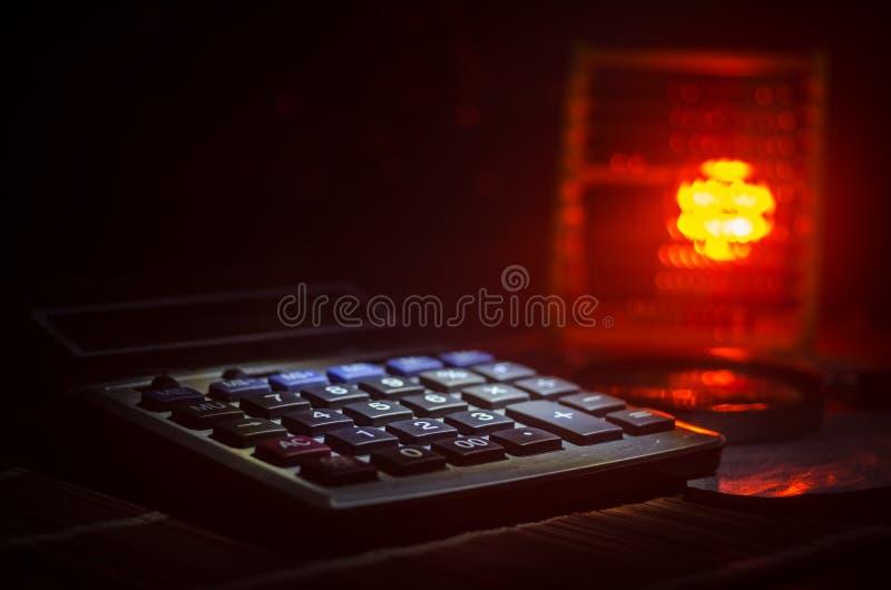 Accessori di affari (lente, calcolatore) e grafici, tavole, grafici su una tavola con fondo scuro Fuoco selettivo fotografia stock