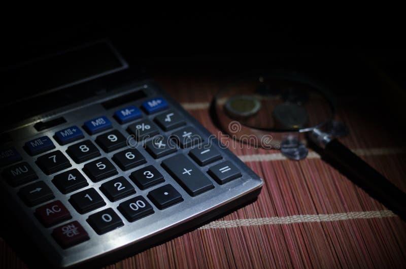 Accessori di affari (lente, calcolatore) e grafici, tavole, grafici su una tavola con fondo scuro Fuoco selettivo immagine stock libera da diritti