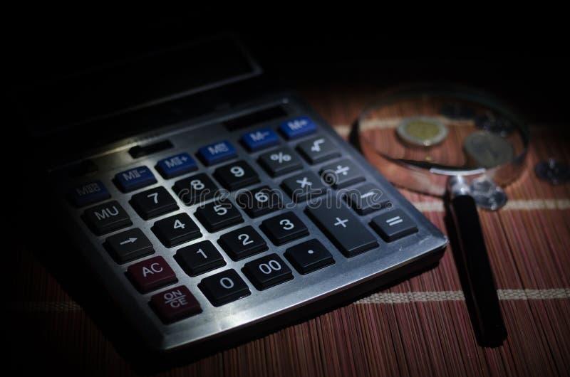 Accessori di affari (lente, calcolatore) e grafici, tavole, grafici su una tavola con fondo scuro Fuoco selettivo fotografia stock libera da diritti