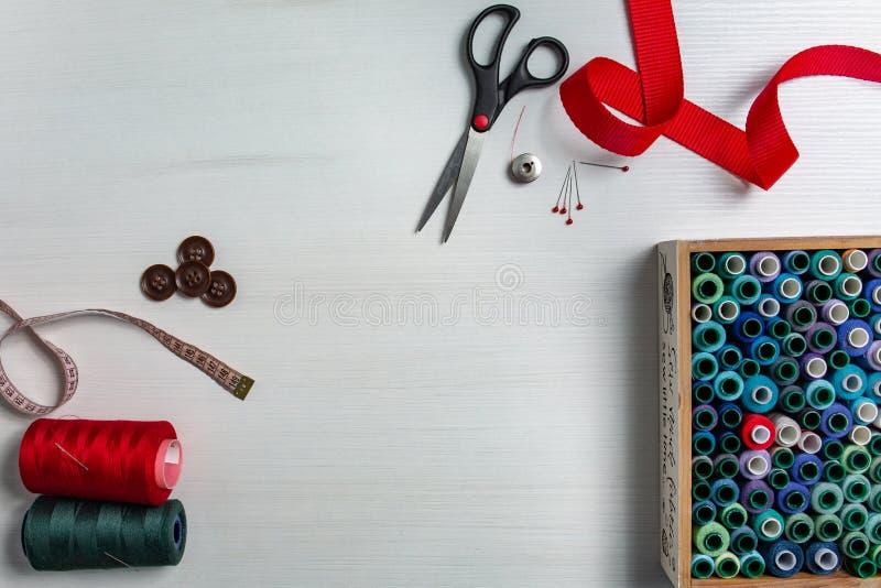 Accessori di cucito su un fondo bianco Scatola con i filati cucirini ed aghi, forbici e bottoni Vista superiore, flatlay immagine stock