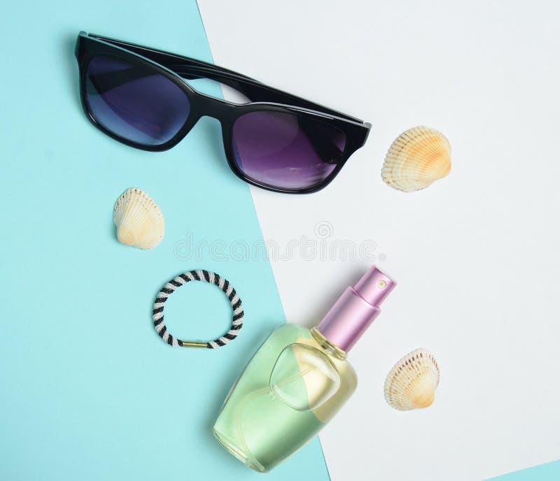 Accessori di modo femminili su un fondo pastello bianco blu Occhiali da sole, bottiglia di profumo, coperture Accessori della spi fotografia stock libera da diritti