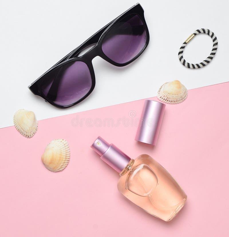 Accessori di modo femminili su un fondo pastello bianco rosa Occhiali da sole, bottiglia di profumo, coperture Accessori della sp immagine stock