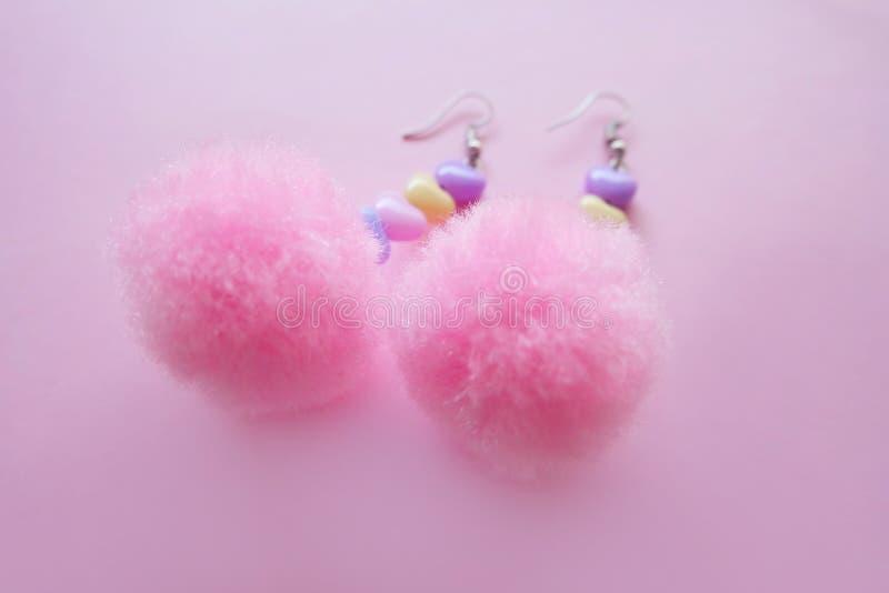 Accessori di modo rotondi rosa dell'orecchino della pelliccia Bello Pom Heart Earring Isolated rosa su fondo rosa fotografie stock