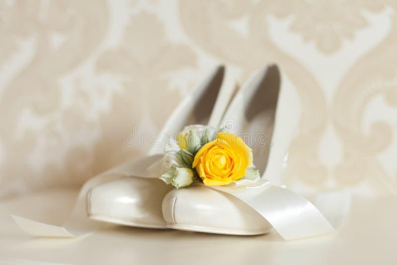 Accessori di nozze del ` s della sposa: scarpe di nozze e mazzo o boutonniere immagini stock