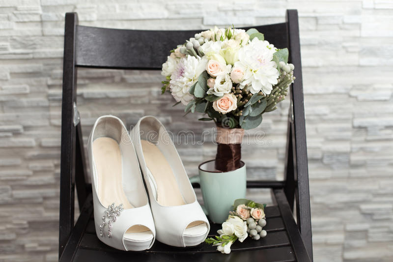 Accessori di nozze del ` s della sposa: scarpe di nozze e mazzo o boutonniere fotografie stock libere da diritti