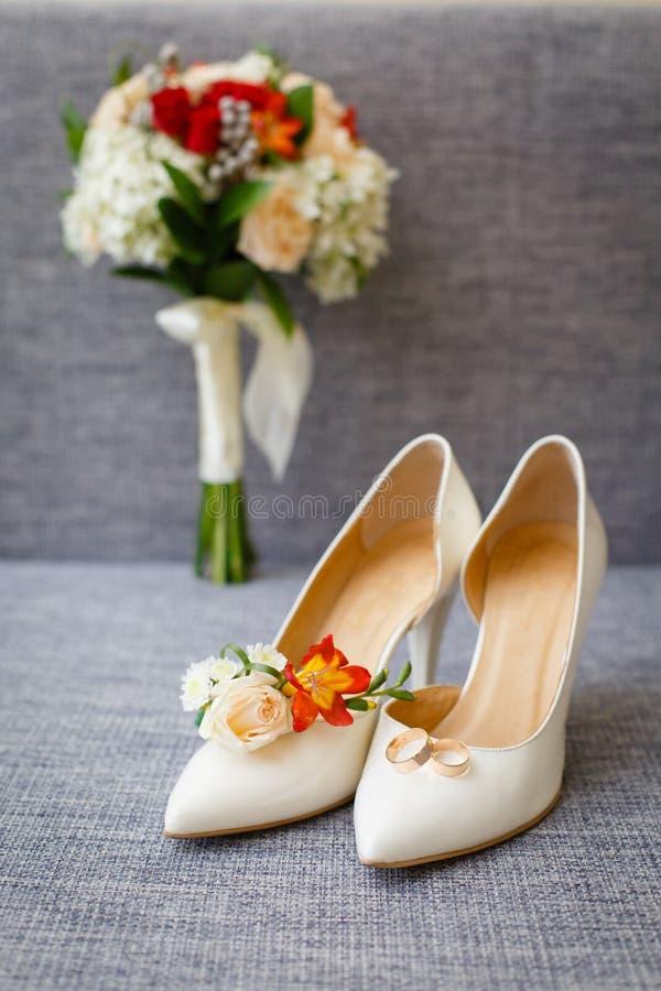 Accessori di nozze del ` s della sposa: scarpe di nozze e mazzo o boutonniere fotografia stock libera da diritti