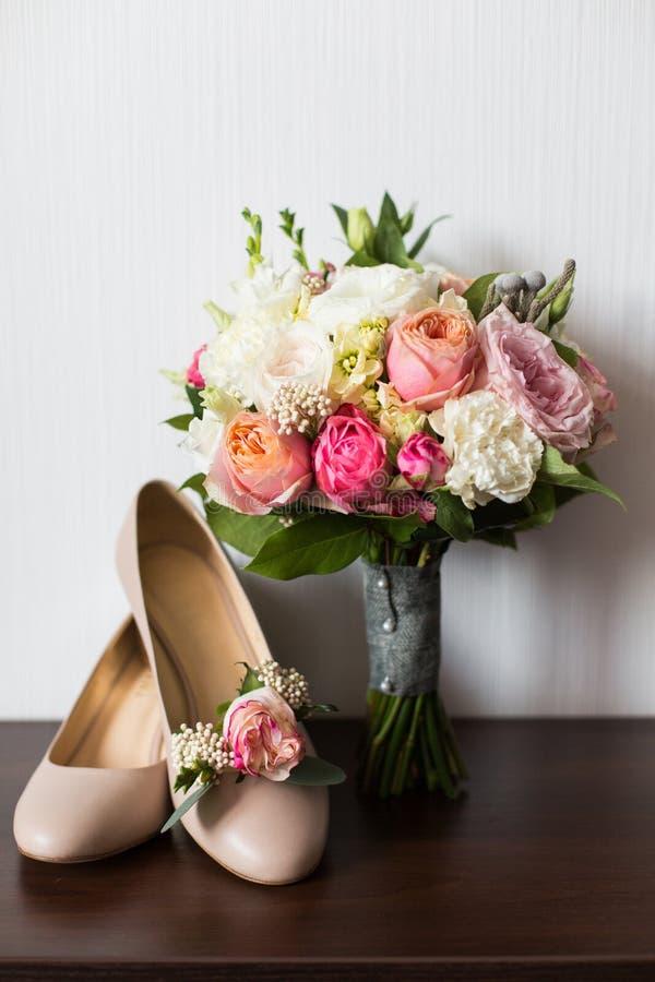 Accessori di nozze del ` s della sposa: scarpe di nozze e mazzo o boutonniere immagine stock