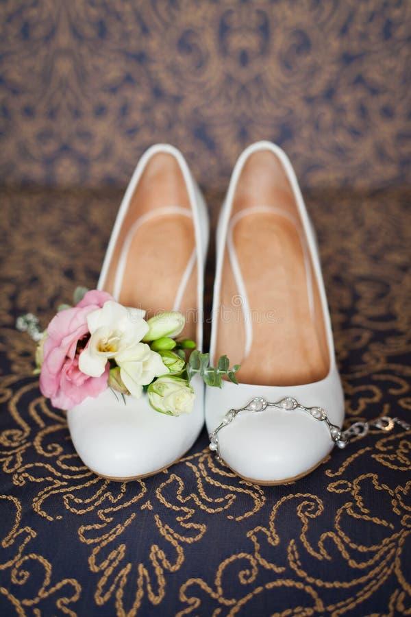 Accessori di nozze del ` s della sposa: scarpe di nozze e mazzo o boutonniere immagini stock libere da diritti