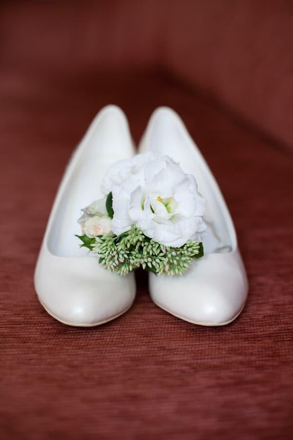 Accessori di nozze del ` s della sposa: scarpe di nozze e mazzo o boutonniere immagine stock libera da diritti
