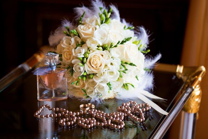 Accessori di nozze Il mazzo, le perle, i profumi e w della sposa fotografia stock libera da diritti