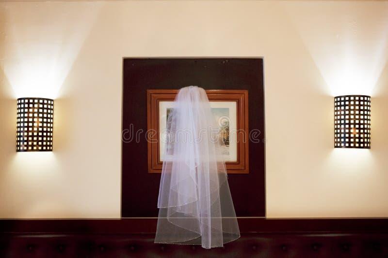 Accessori di nozze Il velo appende sopra il letto fra due lampade immagini stock