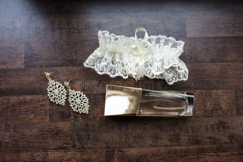 Accessori di nozze Profumo dell'oro, orecchini nuziali con le pietre preziose e giarrettiera bianca immagini stock libere da diritti