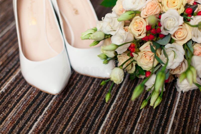Accessori di nozze: scarpe e mazzo del ` s della sposa immagini stock