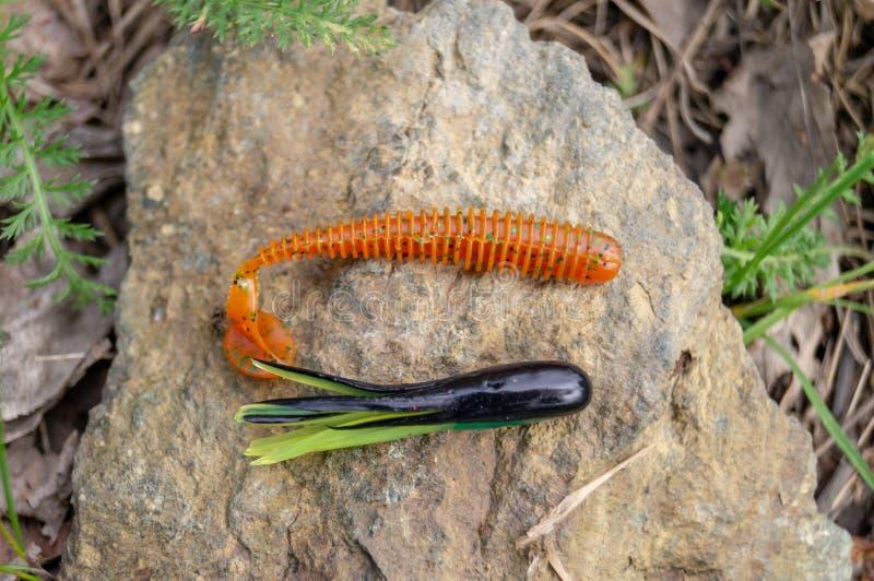 Accessori di pesca Bagattelle e richiami che si trovano su una pietra con un fondo della foresta immagine stock