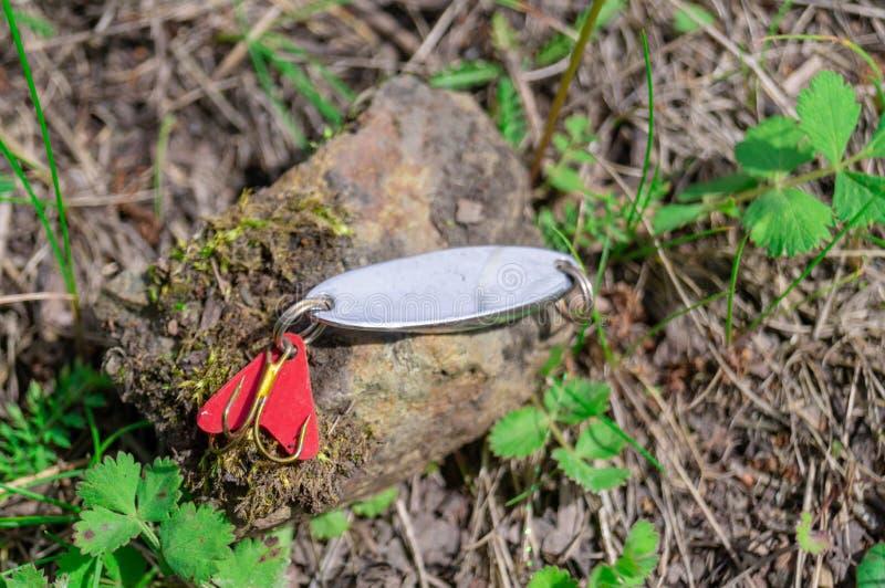 Accessori di pesca Bagattelle e richiami che si trovano su una pietra con un fondo della foresta fotografia stock libera da diritti