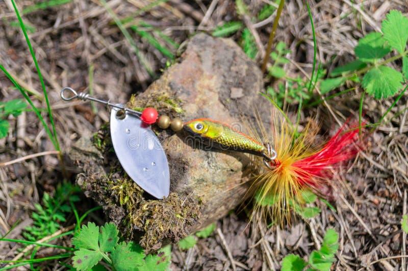 Accessori di pesca Bagattelle e richiami che si trovano su una pietra con un fondo della foresta immagini stock libere da diritti
