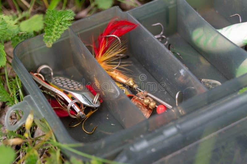Accessori di pesca in una scatola di plastica metta dei filatori e dei richiami fotografia stock libera da diritti