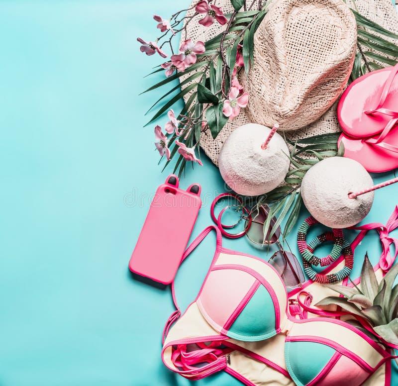 Accessori di vacanza estiva e di viaggio: cappello di paglia, bevande della noce di cocco, bikini e Smart Phone sul fondo del blu fotografia stock libera da diritti
