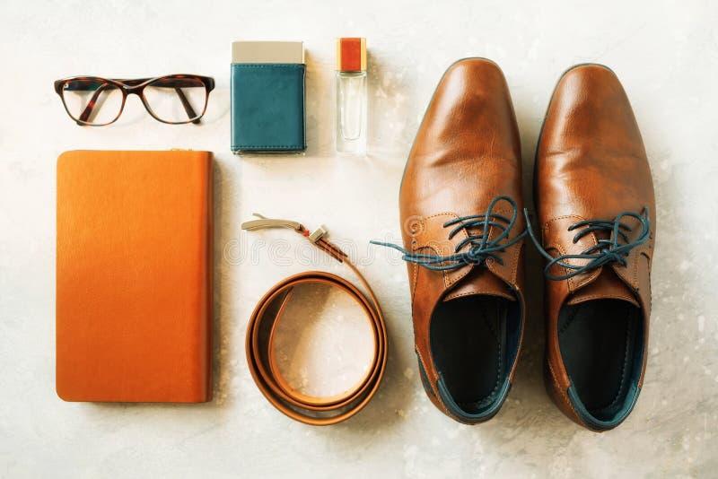 Accessori e scarpe del ` s degli uomini su fondo grigio Disposizione piana della cinghia elegante, vetri, parfume, taccuino Insie fotografia stock