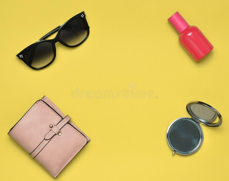Accessori femminili isolati su un fondo giallo Prodotti per bellezza e modo Occhiali da sole, una borsa, una bottiglia di profumo fotografia stock