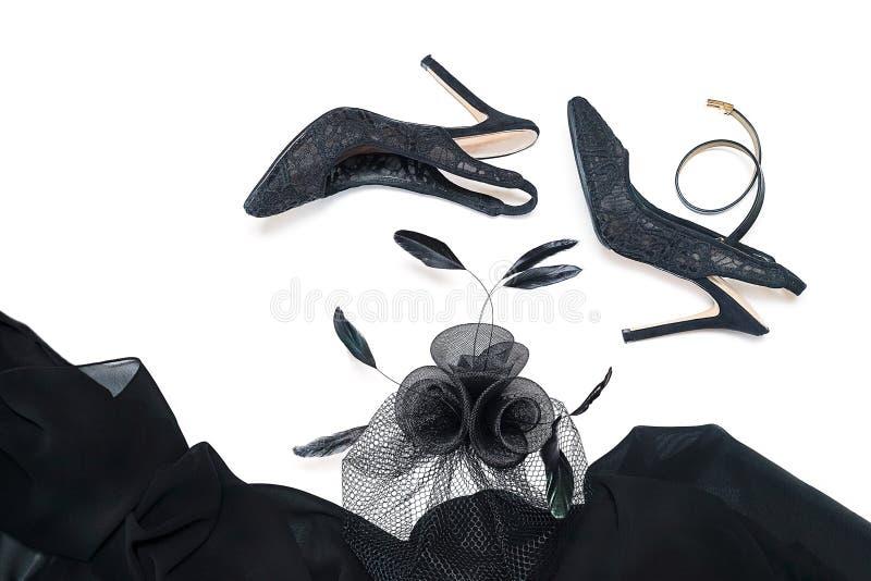 Accessori femminili neri su fondo bianco, scarpe, panno con i crani, gioielli, borsa della raccolta dell'attrezzatura del partito fotografia stock